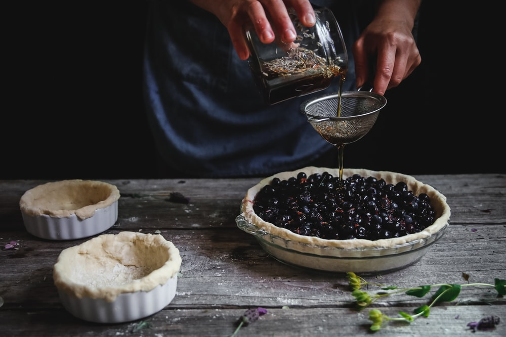 person pouring liquid on blackberry pie