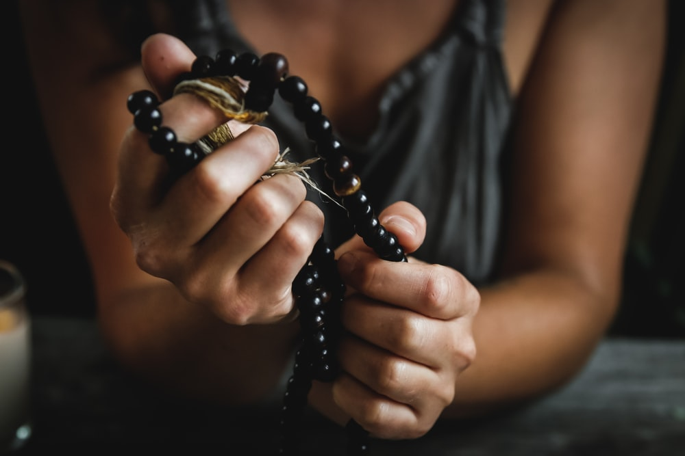 woman holding prayer beads