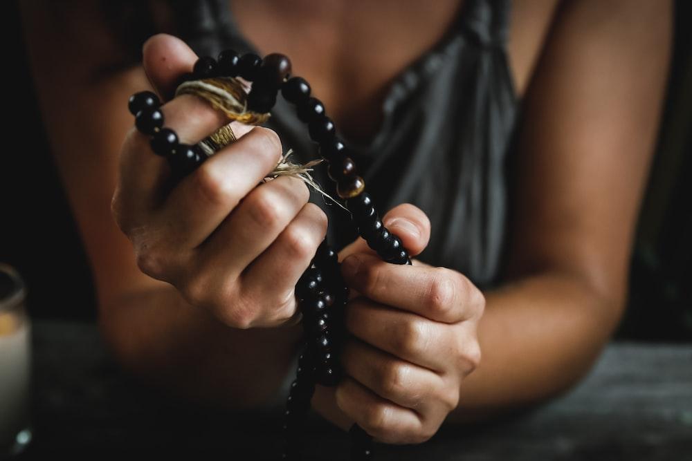 woman holding prayer beads