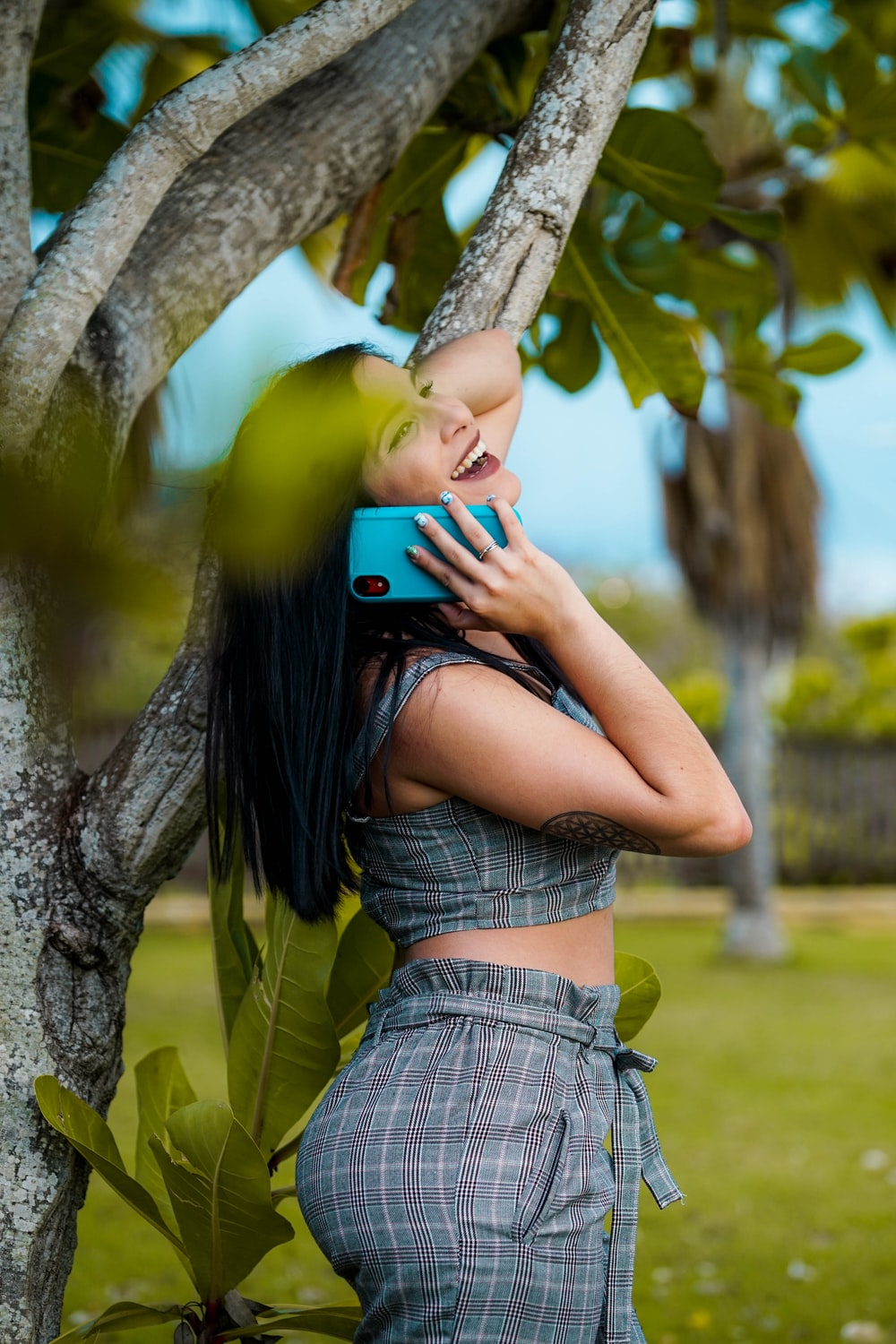 woman listing on to blue smartphone