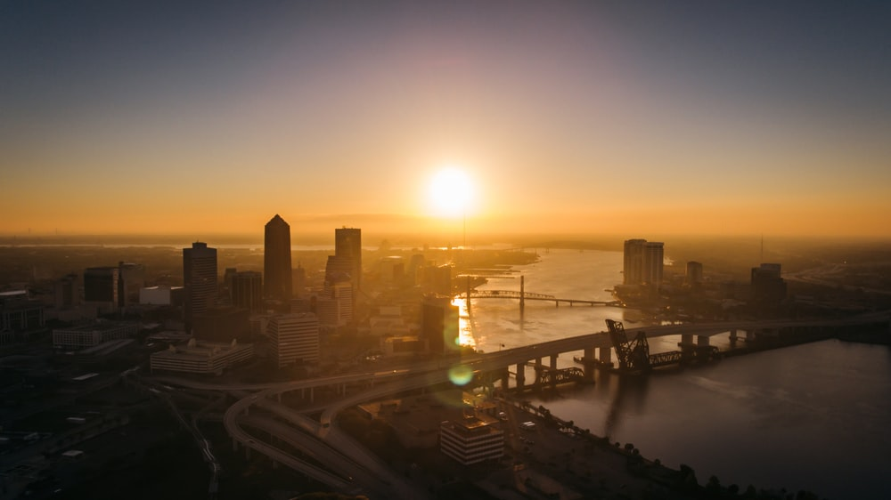 aerial photography of bridge and building beside river during sunset