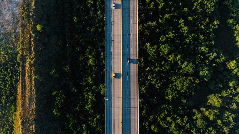 aerial photography of vehicle traveling on bridge during daytime