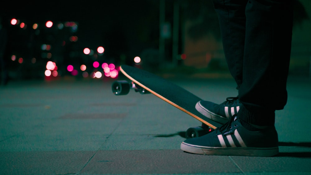 pair of gray-and-white Adidas low-top shoes and gray skateboard