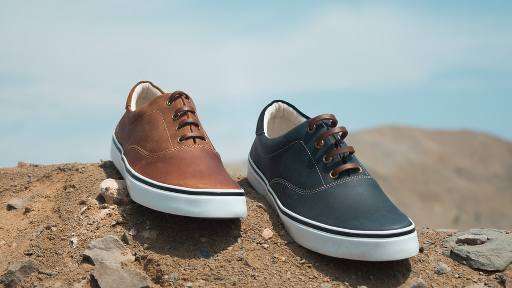 two unpaired brown and blue leather low-top sneakers