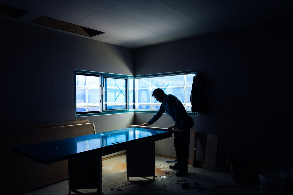 silhouette photography of man inside dim-lighted room