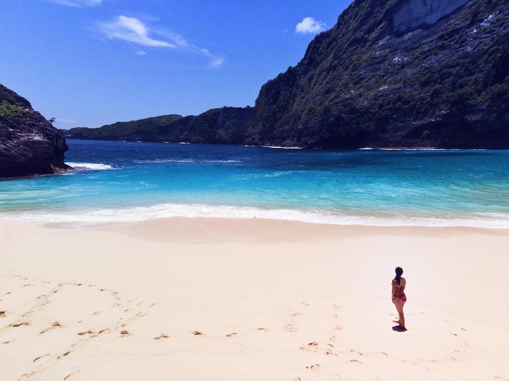 woman standing on seashore during daytime