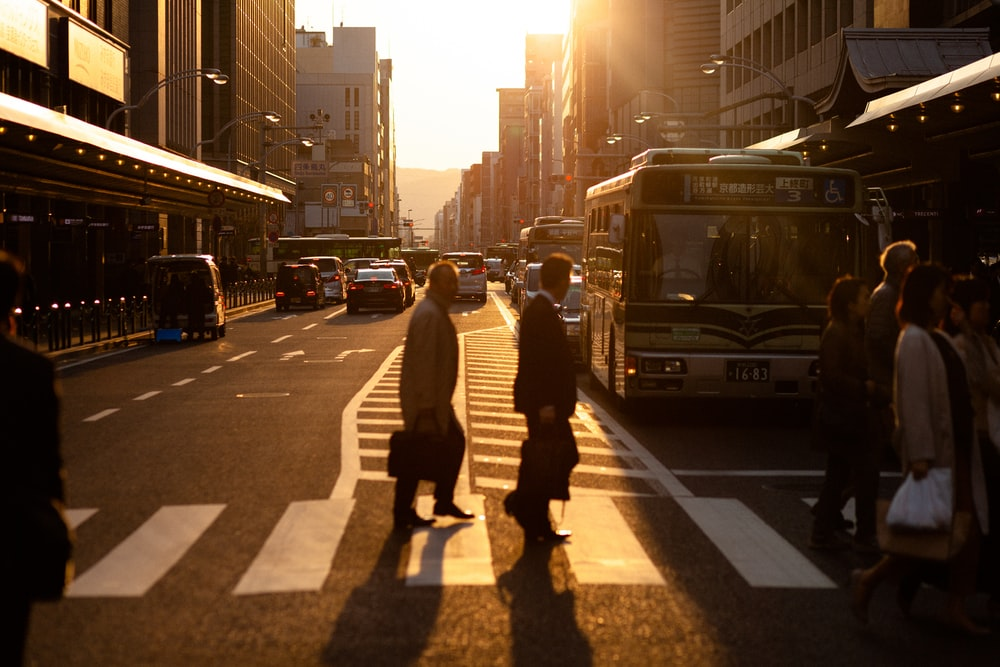 silhouette photography of men crossing pedestrian lane in the city