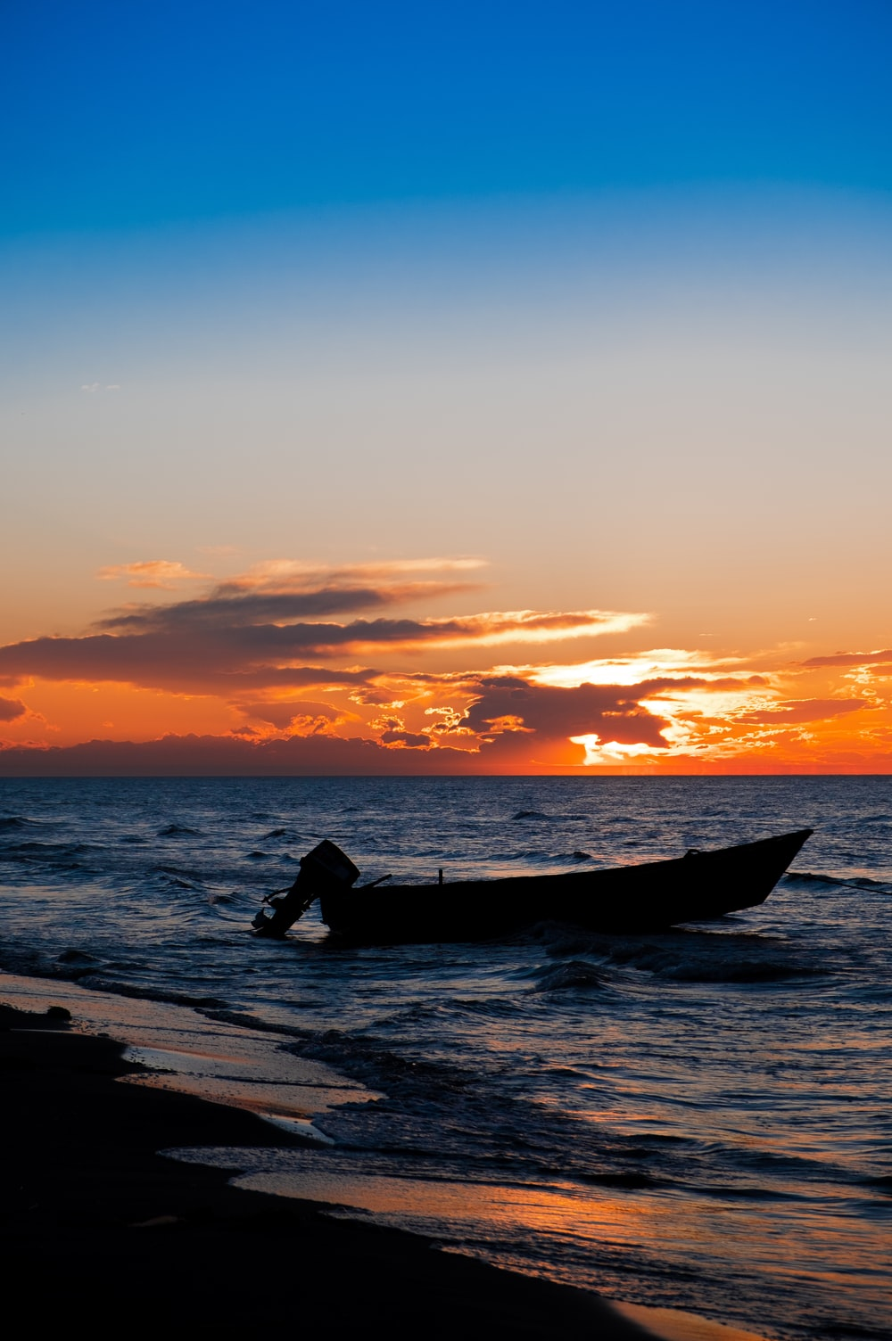 boat on beach line during golden hour
