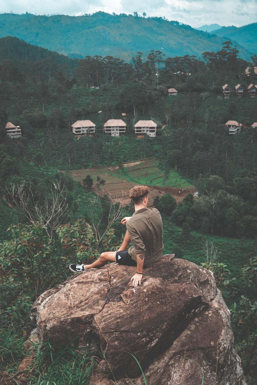 man wearing brown crew-neck shirt sitting on rock