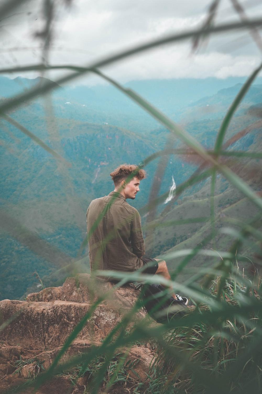 man sitting on mountain top