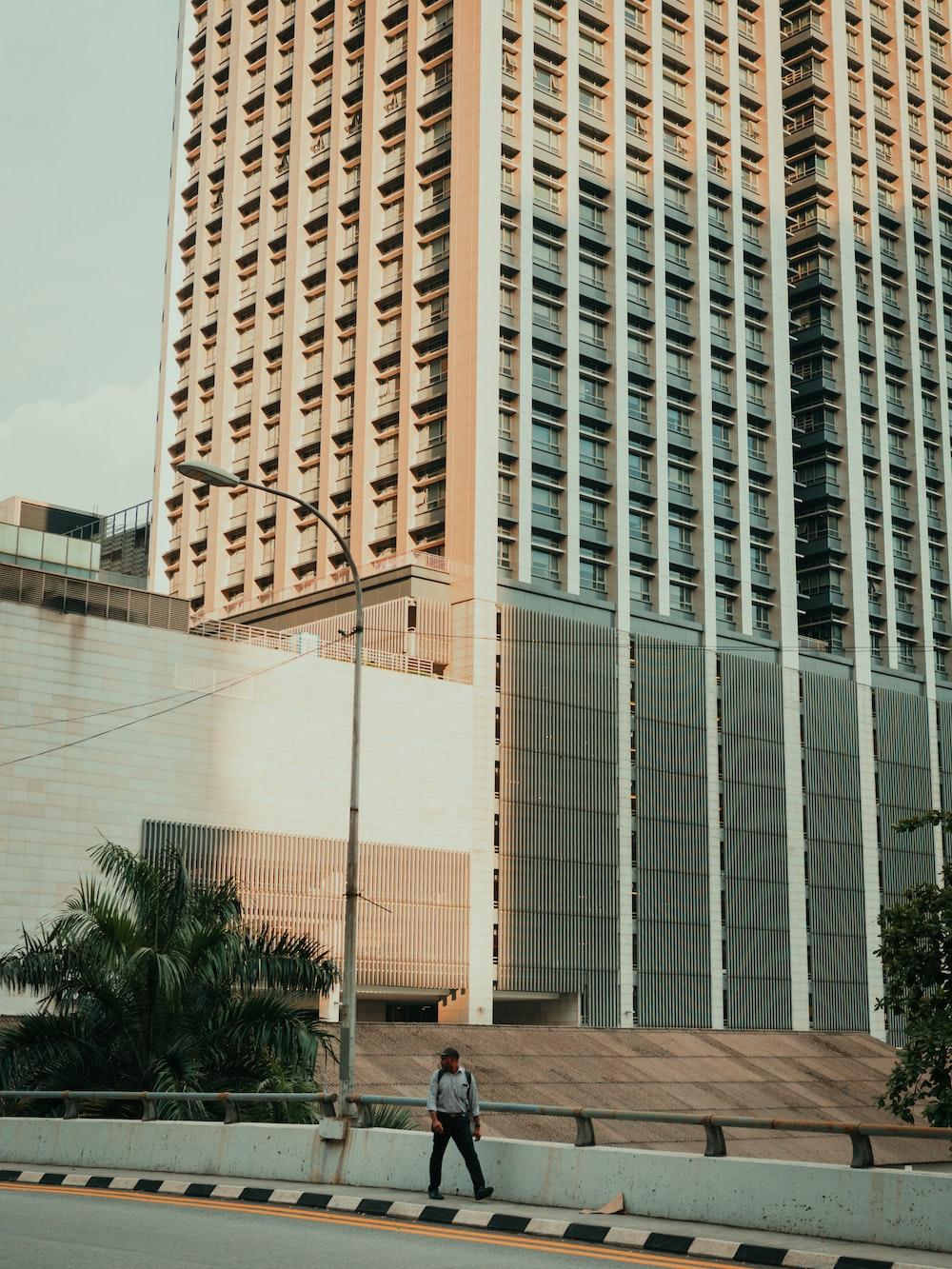 man walking on a concrete bridge in the city