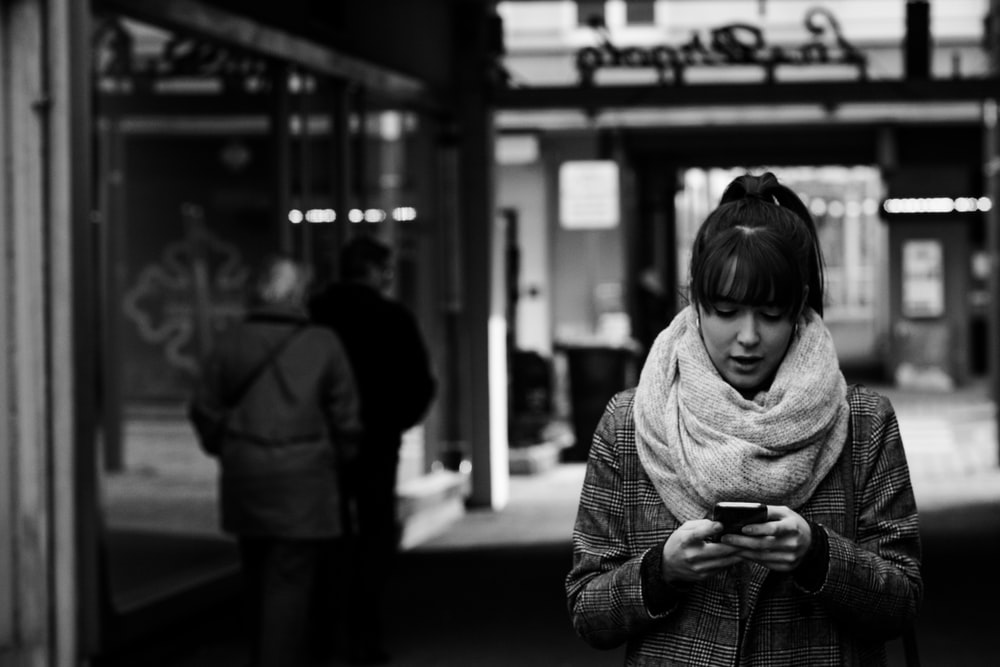 grayscale photography of woman walking near street while using smartphone