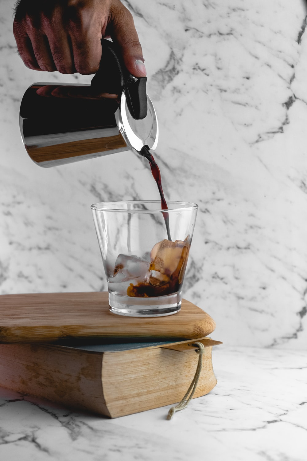 person pouring coffee in cup with ice