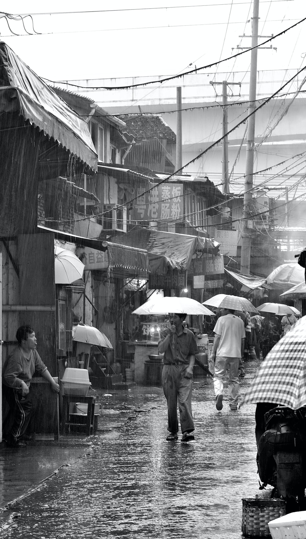 grayscale photography of man holding umbrella