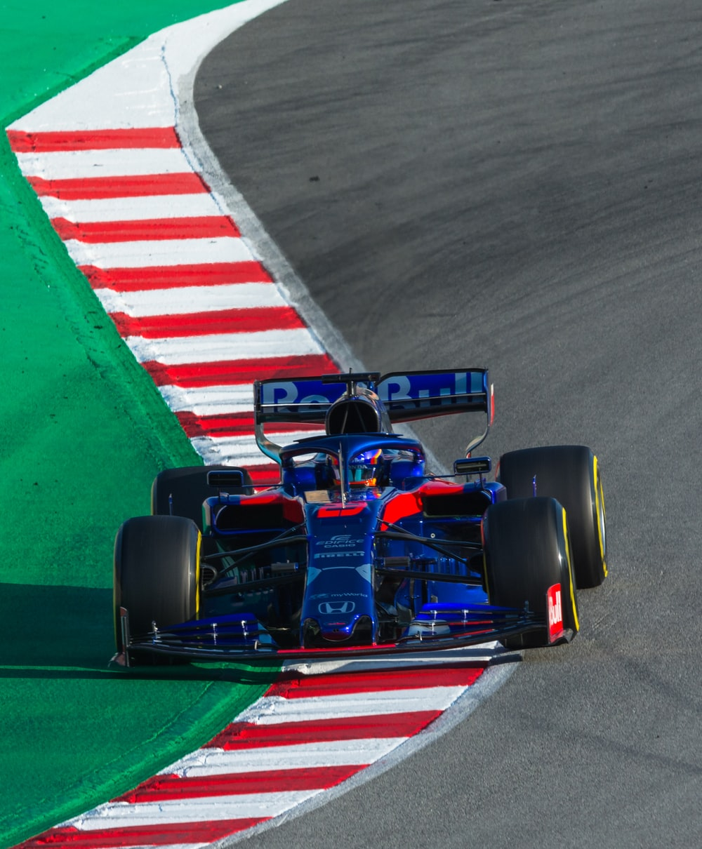 blue F1 car on paved road
