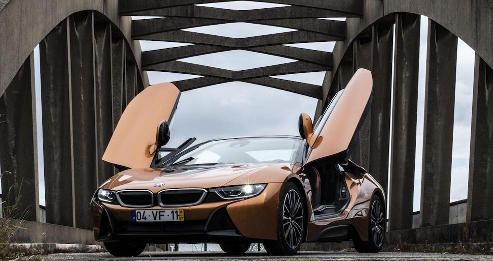 orange BMW i8 parked in middle of bridge