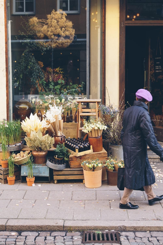 person walking beside flower shop