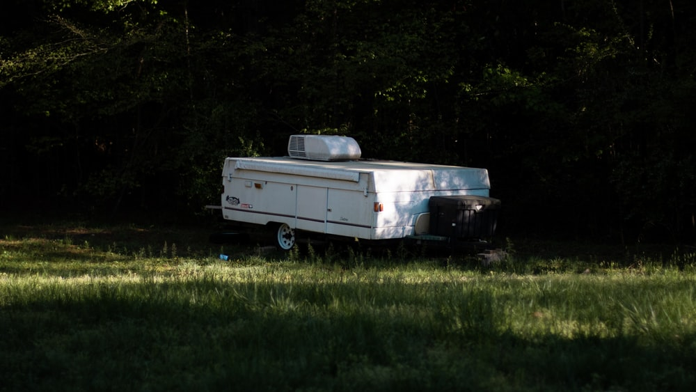 white pop-out camper trailer on grass
