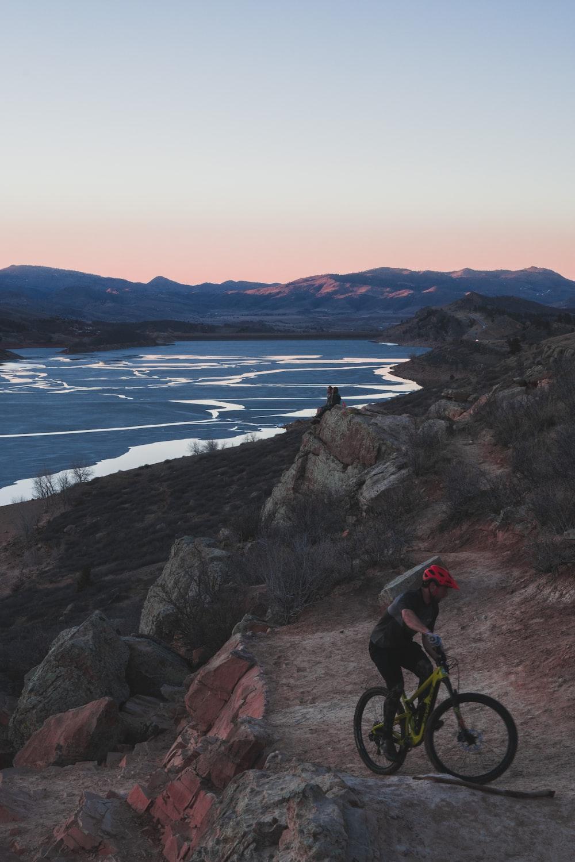 man biking on rocky hill viewing sea