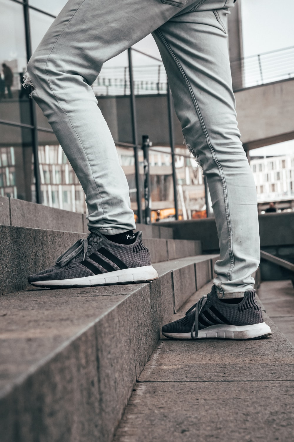 man in grey denim jeans and pair of grey and black Adidas sneakers in stairrs