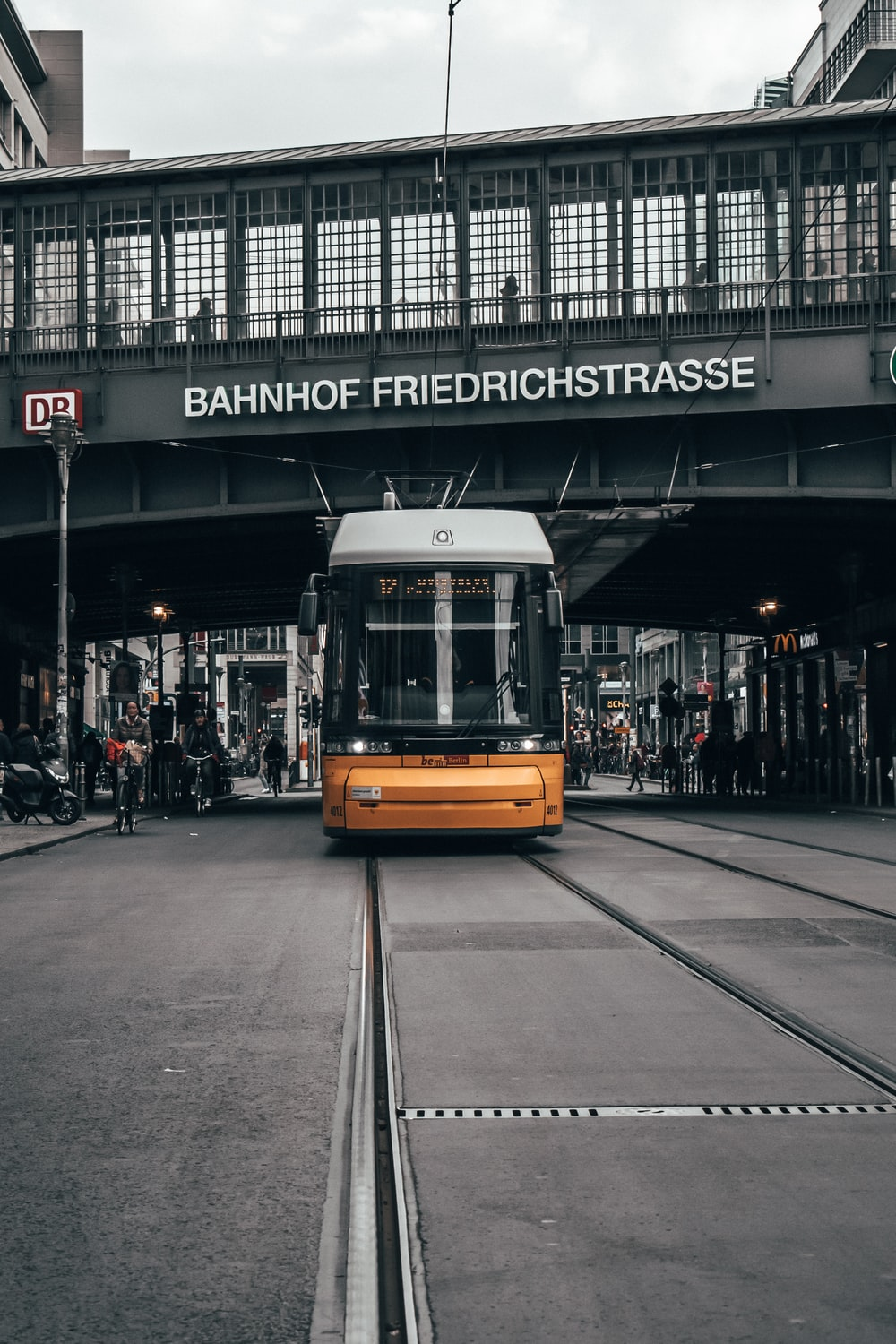 selective focus photography of bus on road under bridge during daytime