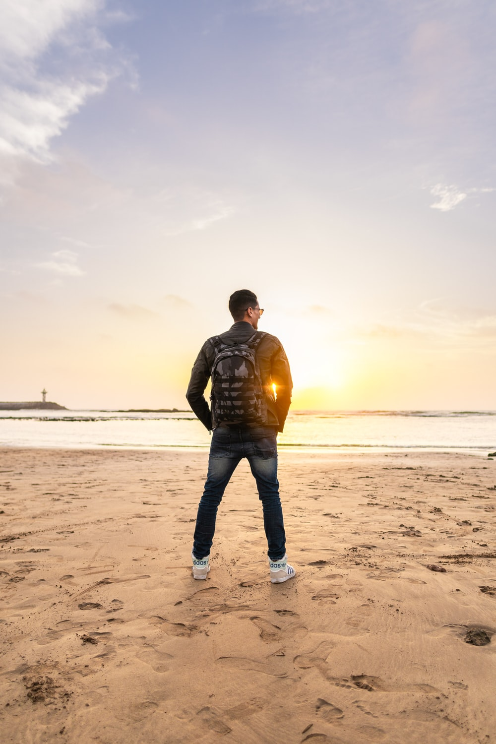 man wearing backpack standing on shore during daytime