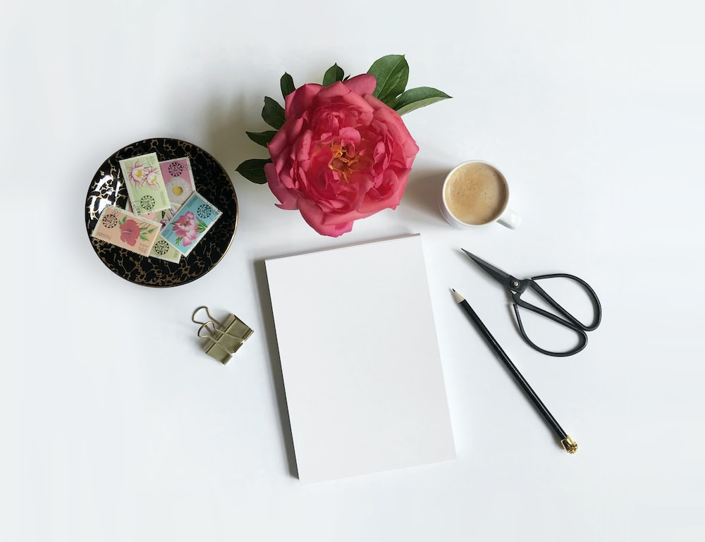 white paper, scissors, pen, coffee, flower, and clip on white surface
