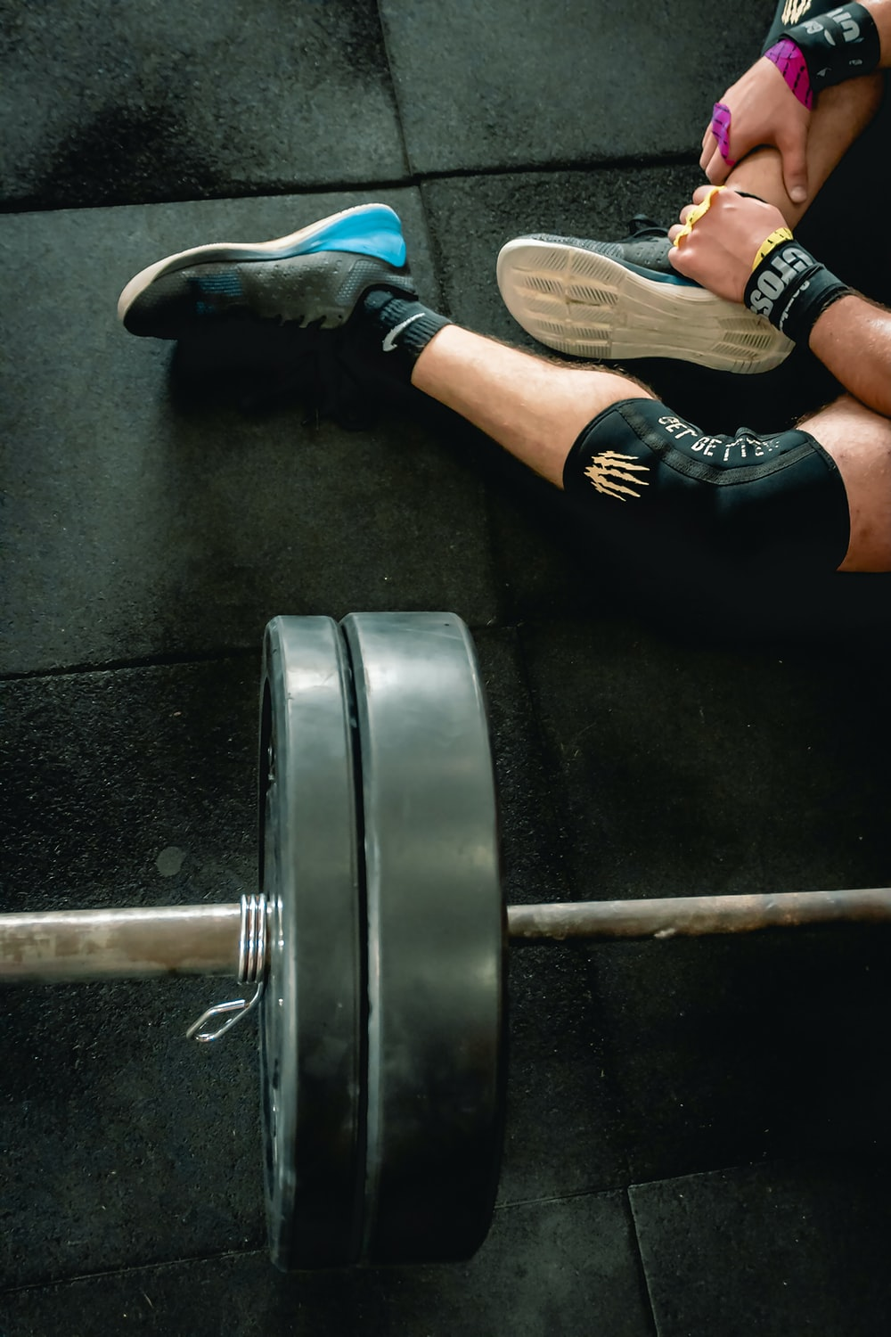 person sitting beside barbell