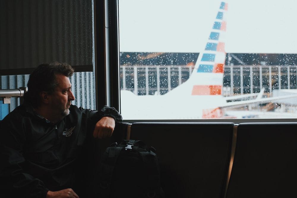 man sitting in airport watching airplane during daytime