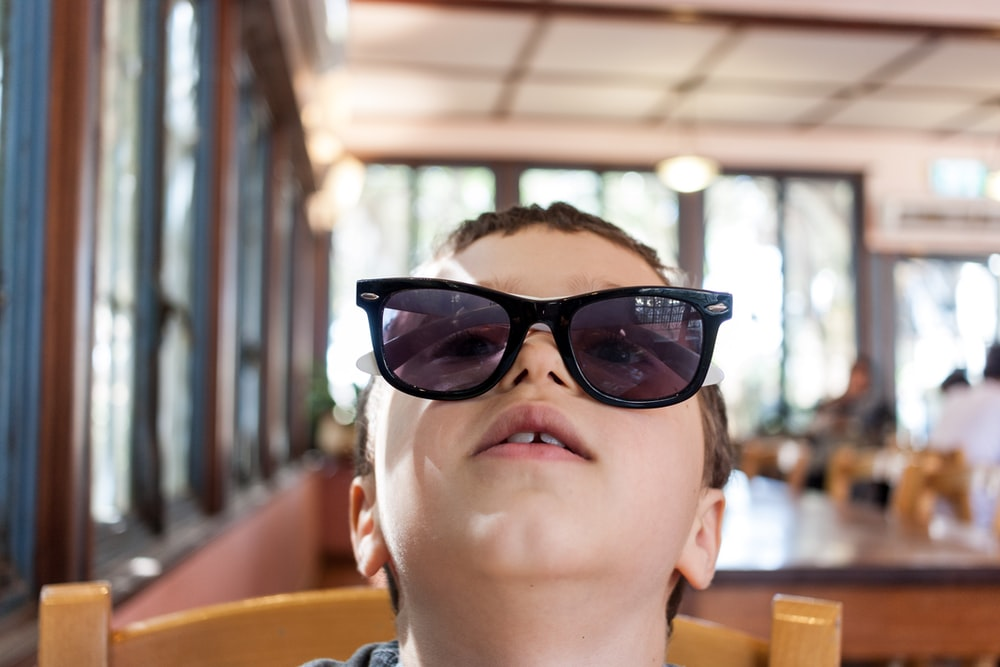 boy wearing sunglasses sitting on brown chair