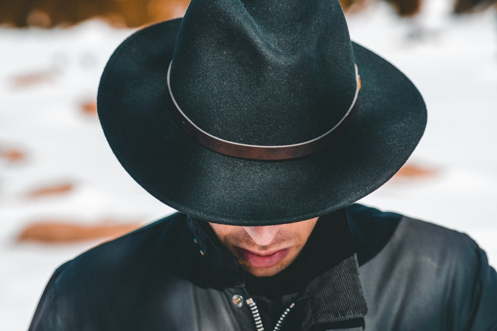 man wearing black jacket and hat looking down