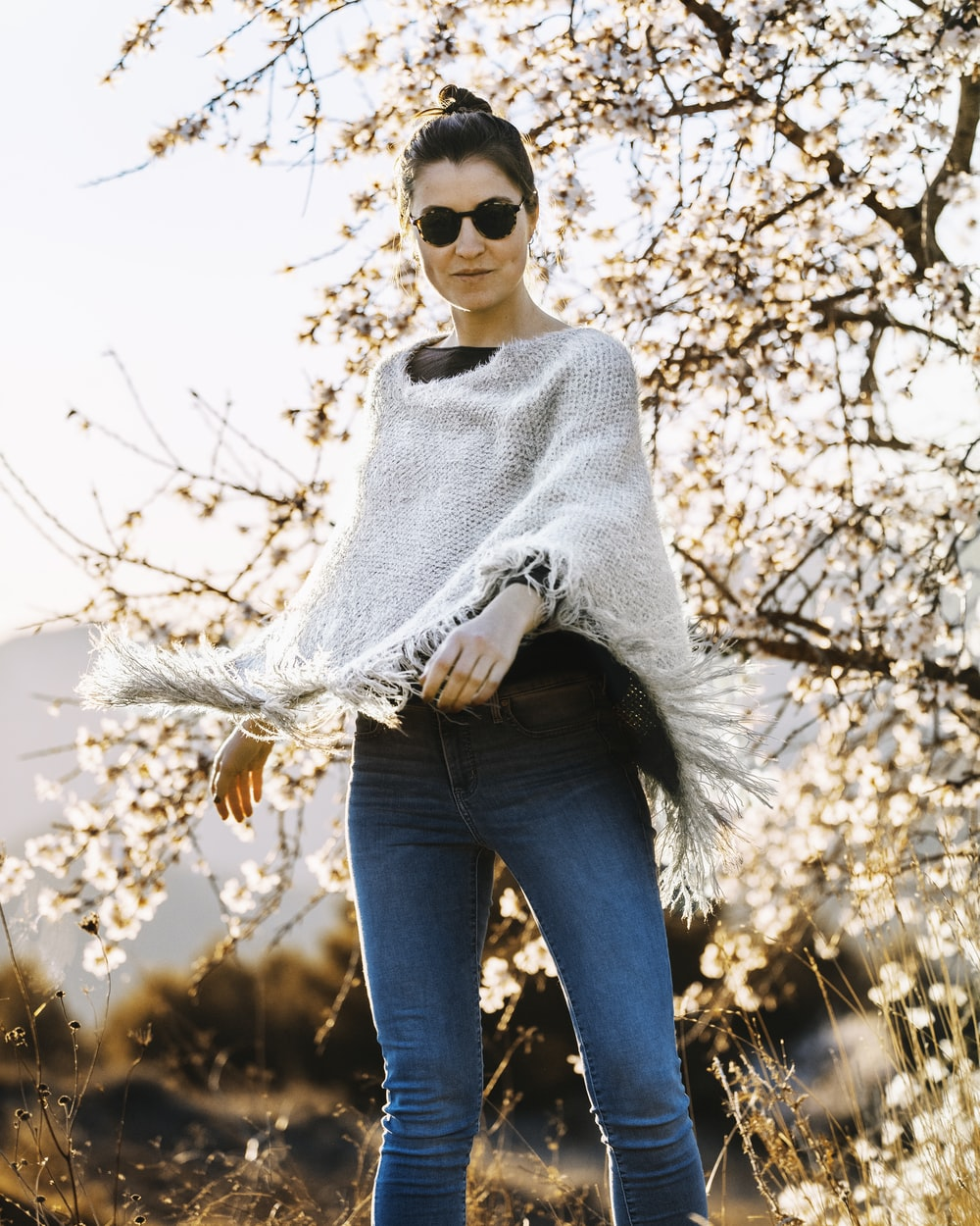 woman in grey poncho standing near cherry blossom tree