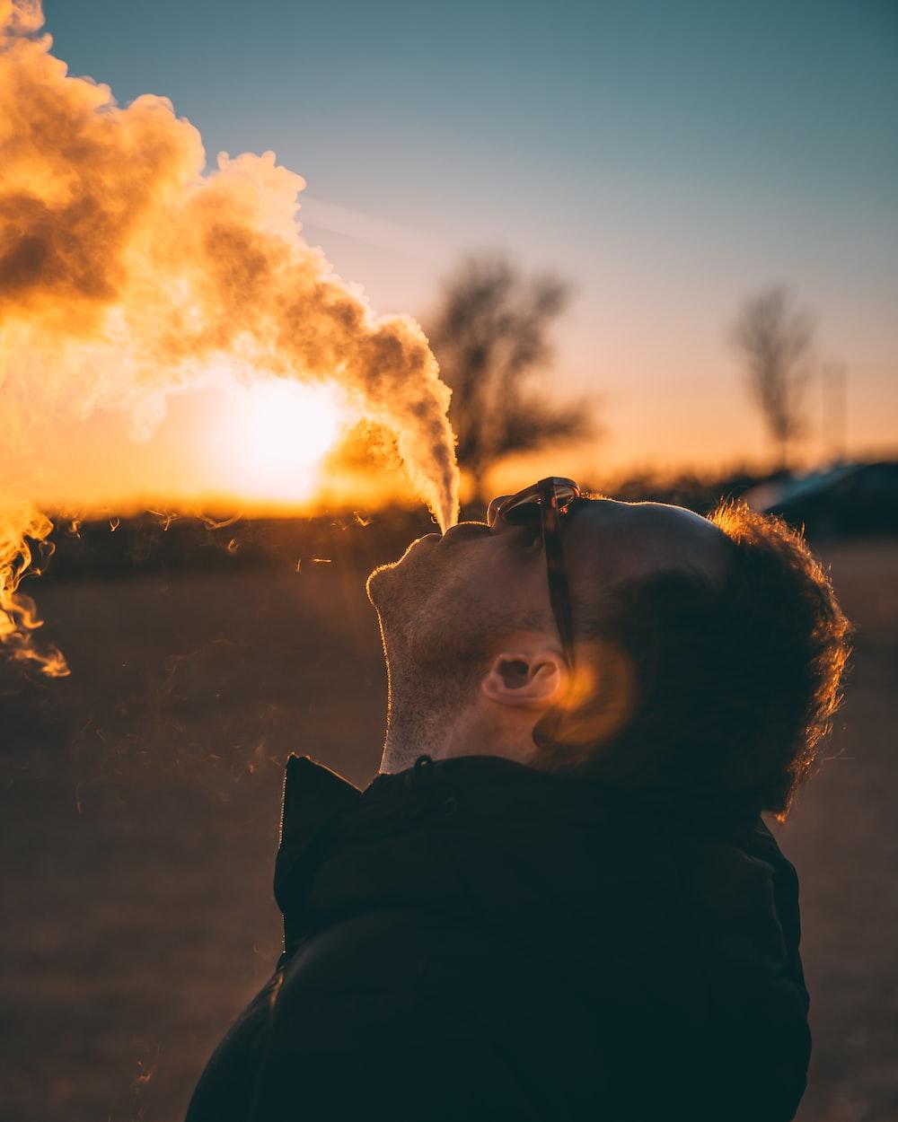 man spewing out smoke at sunset