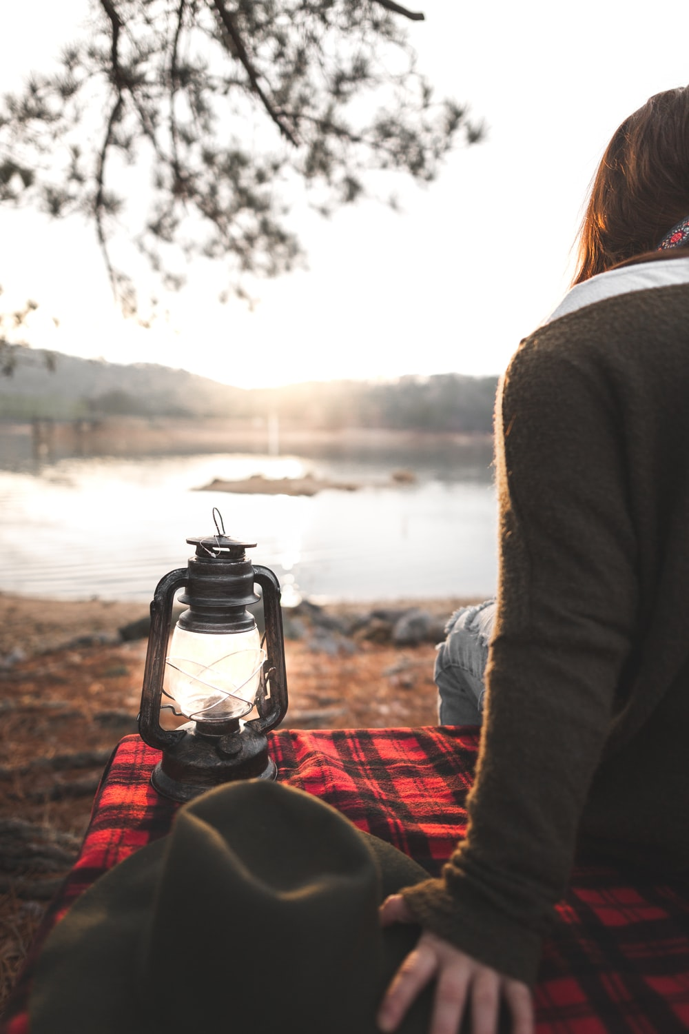 woman sitting on picnic mat with lantern by the lake