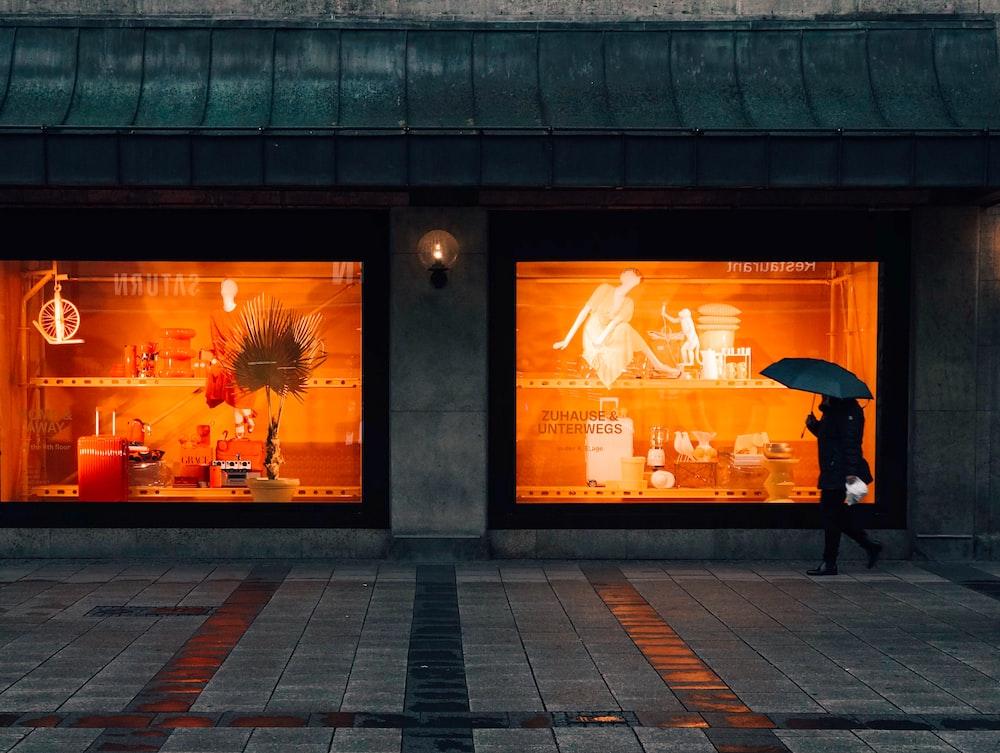 person walking and using umbrella near boutique