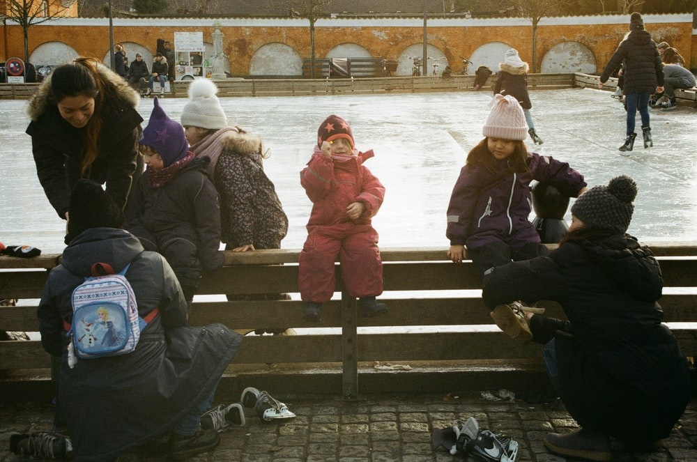 children sitting and others are ice skating on park