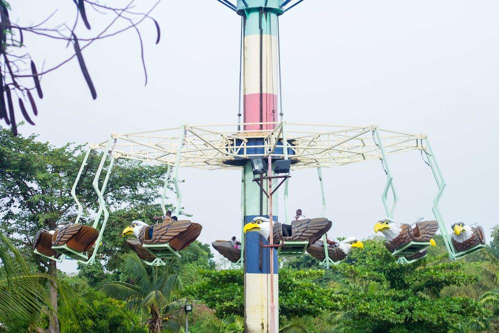 white amusement park ride near trees