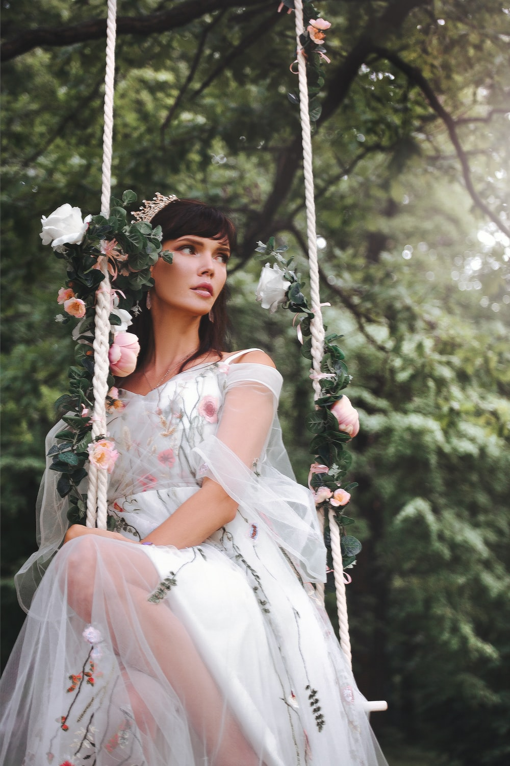 woman wearing wedding gown sitting on outdoor swing near tall trees