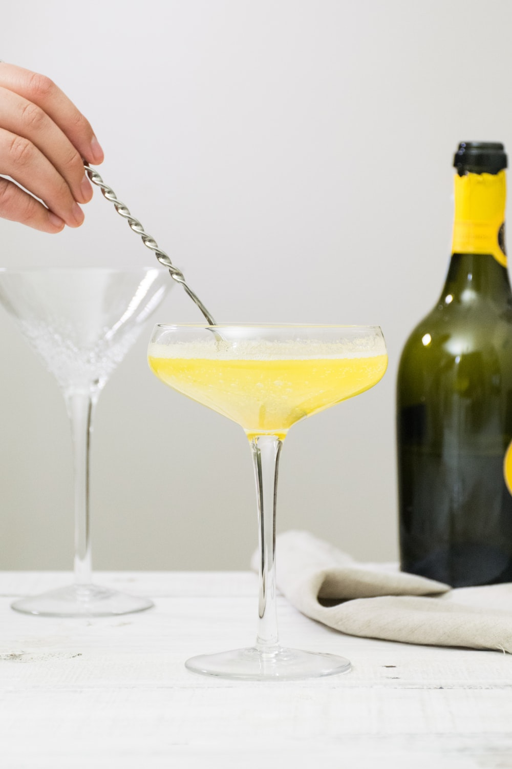 yellow liquid in clear footed glass cup