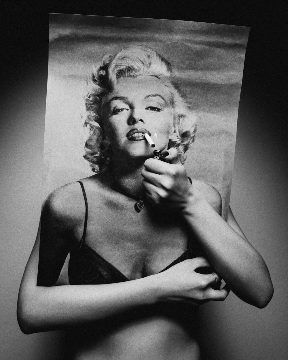 person holding Marilyn Monroe poster covering face