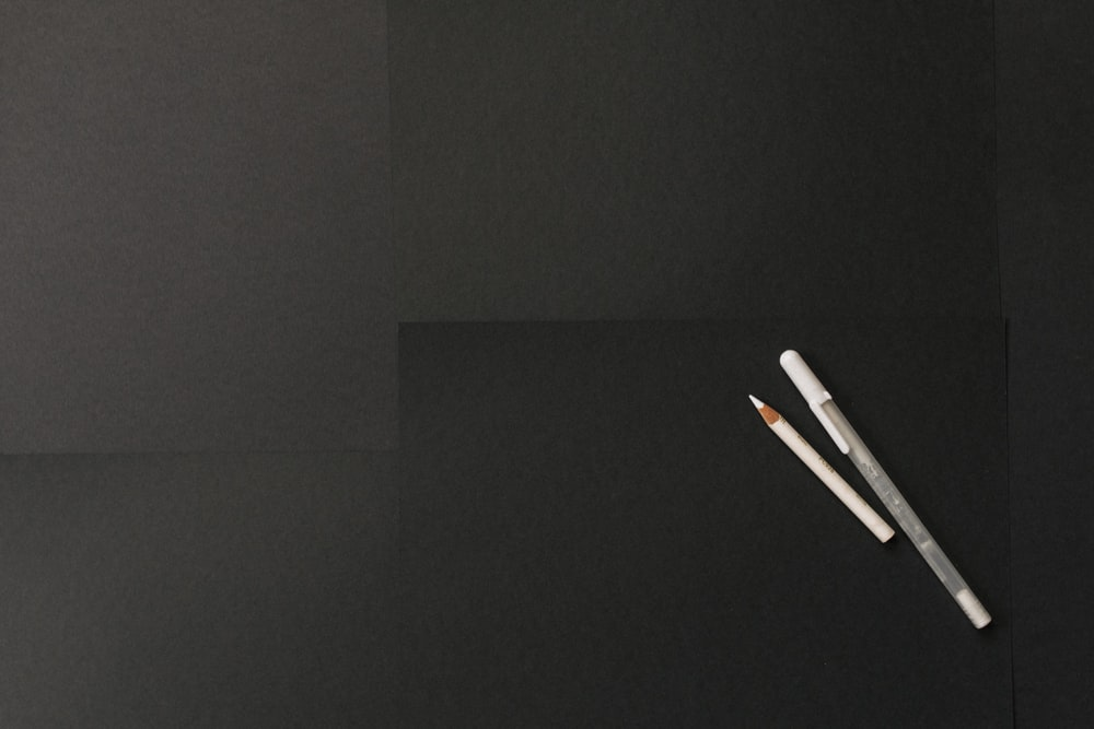 two white pens on black surface