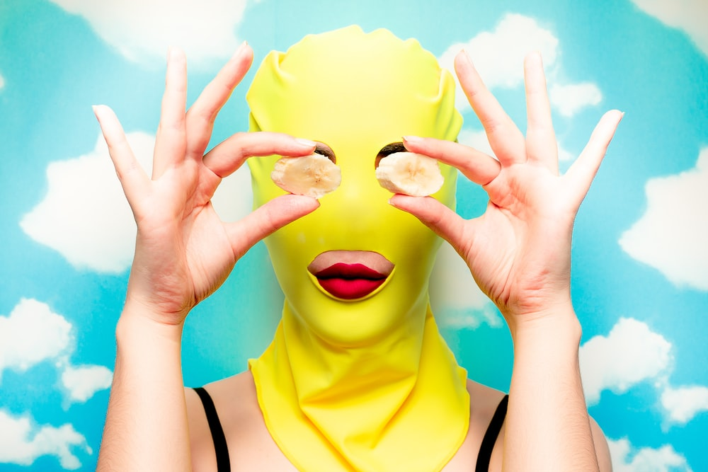 woman wearing yellow mask and covering eyes with two banana slices