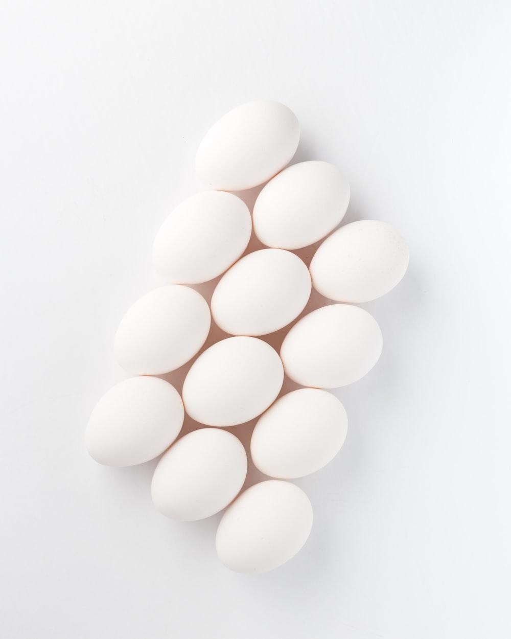 twelve white eggs on white surface