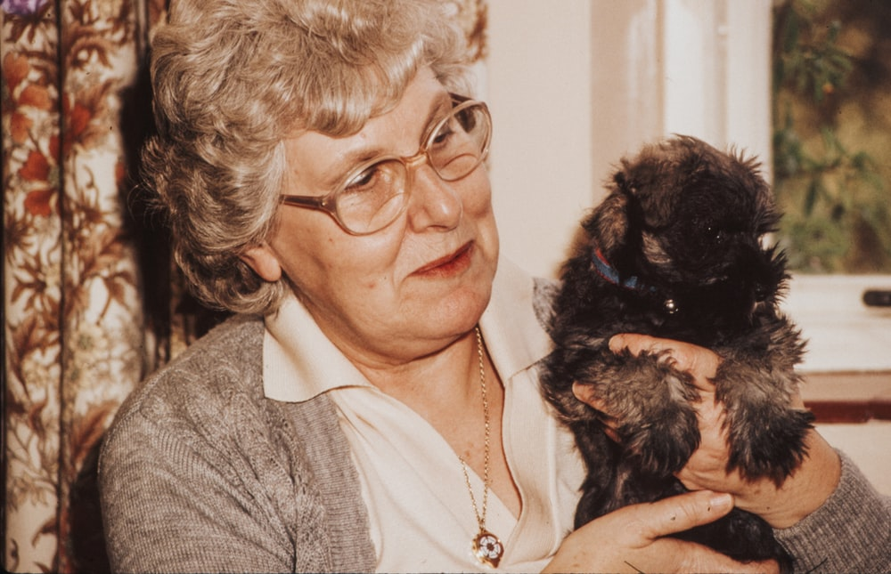 woman carrying black puppy