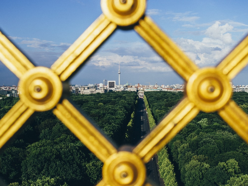 high-angle photography of city during daytime through yellow metal fence