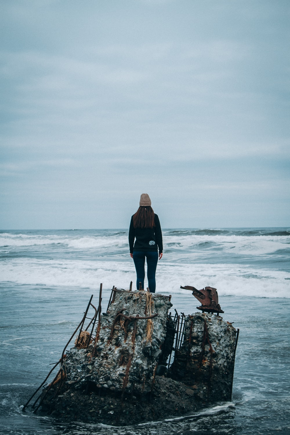 woman standing on rock front of sea