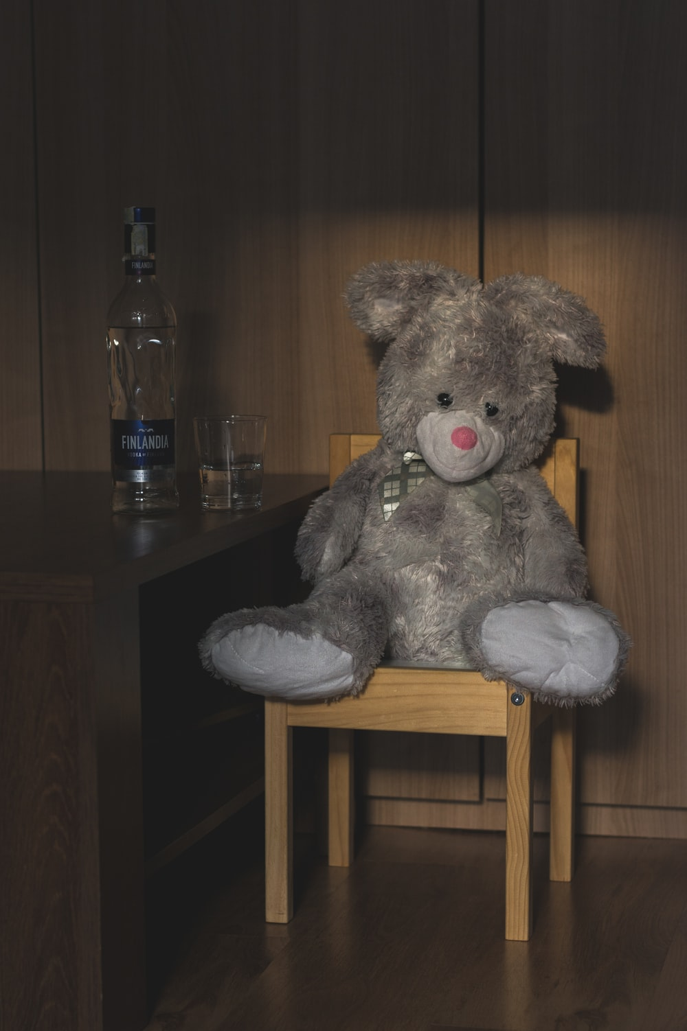 grey bear plush toy on brown wooden chair