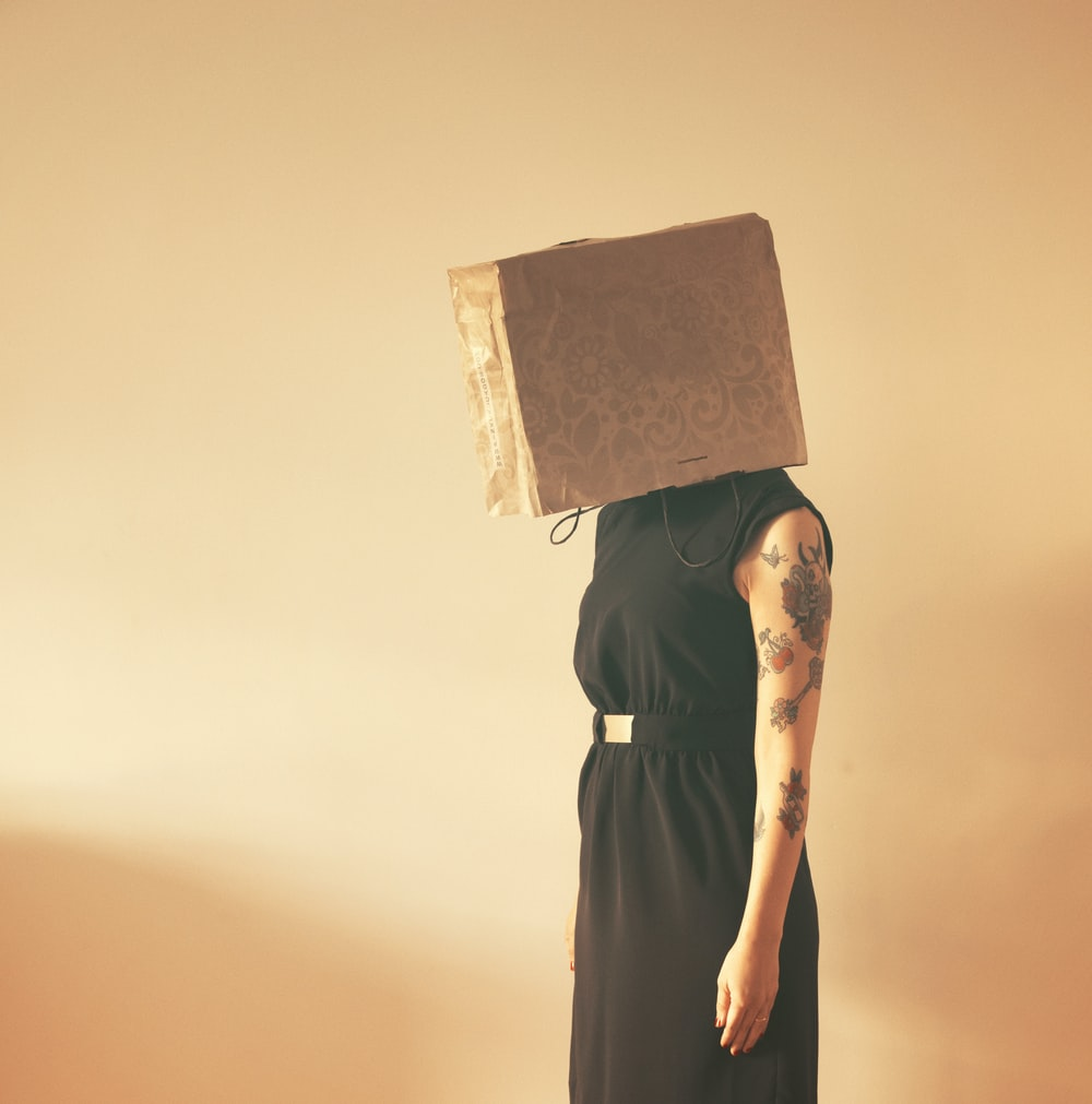 person in black sleeveless dress covered by paper bag