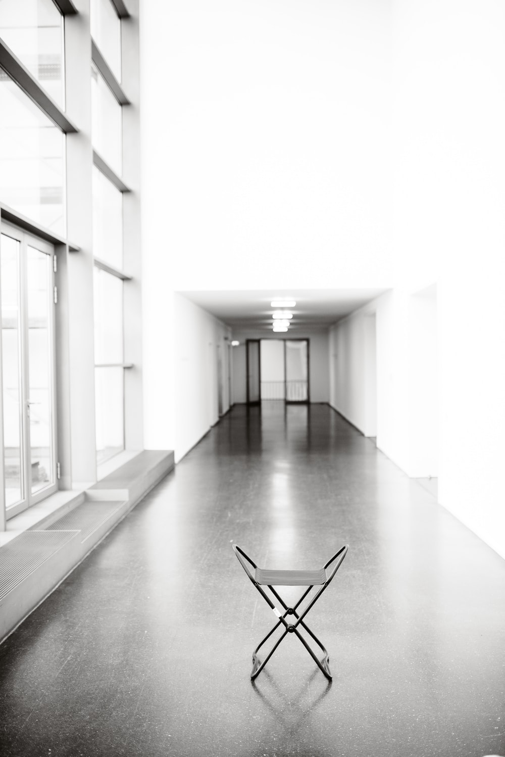 vacant white chair in between hallway of building