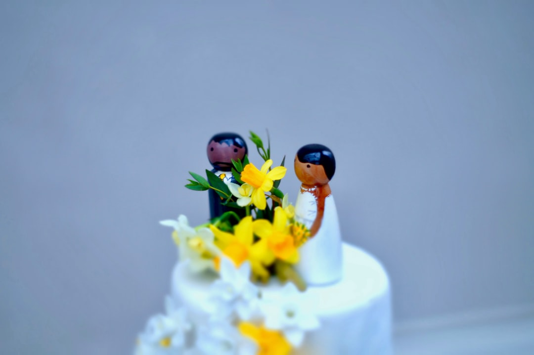 Bride and groom on a white cake with yellow and white daffodil flowers